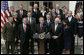 Flanked by members of the Cabinet, President George W. Bush delivers remarks to the media during a press conference Tuesday, March 28, 2006, in the Rose Garden of the White House. White House photo by Paul Morse