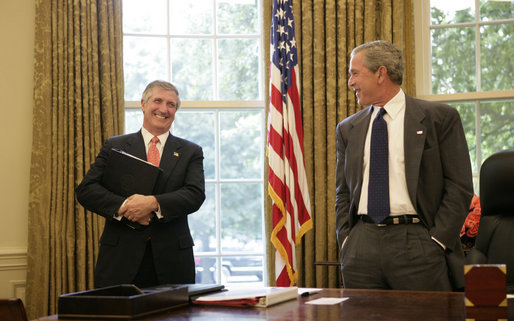 President George W. Bush shares a light moment with Chief of Staff Andrew Card in the Oval Office in this June 2005 file photo. Tuesday, March 28, 2006, the President announced Secretary Card's resignation effective in April. White House photo by Eric Draper