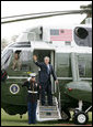 President George W. Bush waves from the steps of Marine One on the South Lawn of the White House, Wednesday, March 29, 2006, as he departs for a three-day summit with the leaders of Mexico and Canada in Cancun, Mexico. White House photo by Shealah Craighead