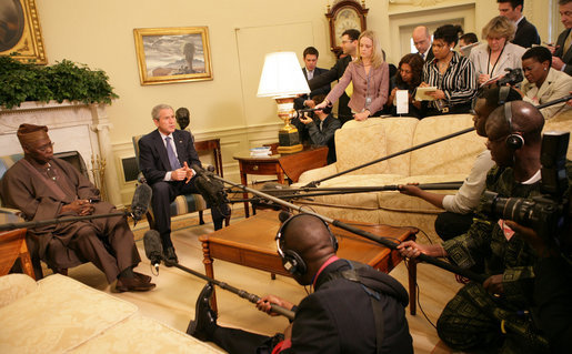 "President George W. Bush speaks to the press as they gather Wednesday, March 29, 2006, in the Oval Office for a photo availability with President Olusegun Obasanjo of Nigeria. President Bush thanked President Obasanjo for his leadership and said, ""Every time I meet with the President he brings a fresh perspective about the politics and the situation on the continent of Africa."" White House photo by Shealah Craighead"