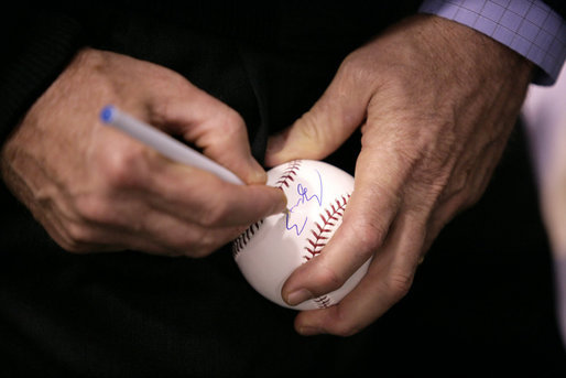 After warming up with a few pitches, President George W. Bush signs a baseball shortly before throwing one over the plate for the opening game between the Cincinnati Reds and the Chicago Cubs in Cincinnati, Ohio, Monday, April 3, 2006. White House photo by Eric Draper