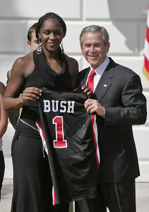 President George W. Bush stands with Crystal Langhorne, captain of the University of Maryland Women's Basketball Team, during a South Lawn ceremony honoring the 2005 and 2006 NCAA champions Thursday, April 6, 2006. The University of Maryland also won national titles in women's field hockey and men's soccer. White House photo by Paul Morse