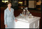 Mrs. Laura Bush poses for a photo next to the State Egg Display which exhibits a decorated egg from a select artist of each state Thursday, April 6, 2006, at the White House Visitor Center. This tradition has been going on since 1994, and each year the artists vote amongst themselves to select the artist to create the following year's commemorative egg which is presented to the President and First Lady. White House photo by Shealah Craighead