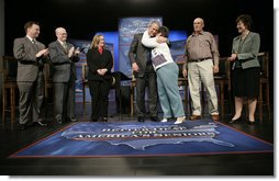 President George W. Bush is embraced by panel member Helen Robinette after concluding a conversation about Medicare prescription drug benefits at the Etta & Joseph Miller Performing Arts Center in Jefferson City, Mo., Tuesday, April 11, 2006. The President and Medicare and Medicaid Services administrator Mark McClellan, far left, met with several Missourians. They are, from left, Gerald Sooter, Jodie Baker, Helen Robinette, Bob Vanderfeltz and Linda Detring.  White House photo by Eric Draper