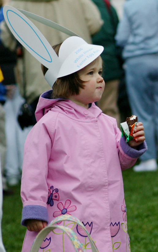 A young child wears her bunny hat and enjoys some candy while strolling the South Lawn of the White House during the 2006 White House Easter Egg Roll, Monday, April 17, 2006. White House Photo by Julie Kubal