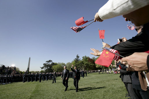 Guests wave flags for Presidents George W. Bush and Hu Jintao during an arrival ceremony held on the South Lawn for the Chinese President, Thursday, April 20, 2006. White House photo by Eric Draper