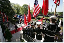 Flags are raised high as President George W. Bush and Mrs. Laura Bush make their way from the White House South Portico to participate in the South Lawn Arrival Ceremony for Chinese President Hu Jintao, Thursday, April 20, 2006. White House photo by David Bohrer