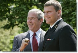 President George W. Bush sports an oversized championship ring as the stands with Midshipman Jeremy Chase of the United States Naval Academy football team during the presentation of the Commander-in-Chief Trophy to in the Rose Lawn April 25, 2006. White House photo by Paul Morse