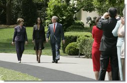"President George W. Bush and Mrs. Laura Bush accompany 2006 National Teacher of the Year Kim Oliver to the South Lawn ceremony in her honor Wednesday, April 26, 2006. Said the President of the Silver Spring, Maryland kindergarten teacher, ""Kim Oliver understands that the key to helping children succeed is fighting the soft bigotry of low expectations."" White House photo by Paul Morse"