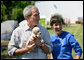 President George W. Bush holds the offspring of a stray dog during a tour of the animal rescue area of the Hands On Network base camp in Biloxi, Mississippi, Thursday, April 27, 2006. Pictured with the President is Disaster Response Coordinator Erika Putinsky. White House photo by Eric Draper