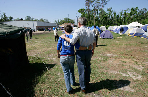 President George W. Bush walks with Hands On Network Disaster Response Coordinator Erika Putinsky during a tour of their base camp in Biloxi, Mississippi, Thursday, April 27, 2006. White House photo by Eric Draper