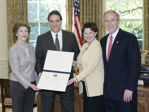 President George W. Bush and Mrs. Bush present the Preserve America award for private preservation to Judy Christa-Cathey, Vice President Brand Management, and Scott Douglas Schrank, Vice President Brand Performance and Support, both of Hampton Hotels' nationwide Save-A-Landmark program, in the Oval Office Monday, May 1, 2006. White House photo by Eric Draper