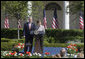 Mrs. Laura Bush and President George W. Bush address guests in the Rose Garden during an event honoring the recipients of the Preserve America Presidential Awards May 1, 2006. White House photo by Kimberlee Hewitt