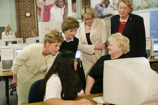 Mrs. Laura Bush and U.S. Department of Education Secretary Margaret Spellings, center, look at computer information with St. Boniface sixth-graders and senior citizens Tuesday, May 2, 2006 in Ft. Smith, Ark., to remind seniors of the May 15th enrollment deadline to sign-up for the Medicare Prescription Drug Benefit. White House photo by Shealah Craighead