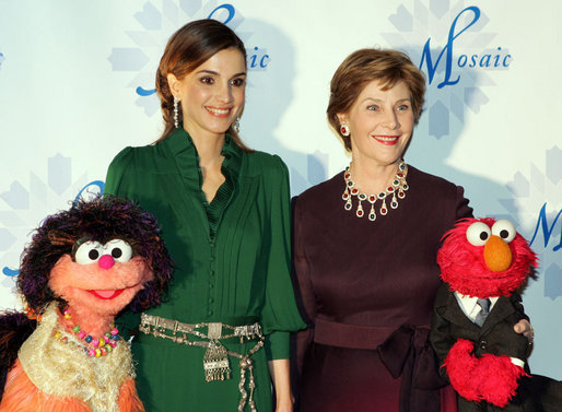Mrs. Laura Bush stands with Her Majesty Queen Rania Al-Abdullah of Jordan and Sesame Street characters Khokha, left, and Elmo during a dinner celebrating the partnership between the Sesame Workshop and the Mosaic Foundation at the National Building Museum in Washington, D.C., Wednesday, May 9, 2006. Founded by the spouses of Arab Ambassadors to the United States, the Mosaic Foundation is dedicated to improving the lives of women and children. White House photo by Shealah Craighead