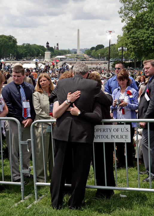 President George W. Bush embraces law enforcement family members during an emotional moment at the Annual Peace Officers' Memorial Service at the U. S. Capitol Monday, May 15, 2006. The service honors fallen federal, state and local law enforcement officers. White House photo by Kimberlee Hewitt