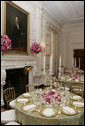A portrait of President Abraham Lincoln is seen above the fireplace in the State Dining Room of the White House, as tables are set and decorated Tuesday, May 16, 2006, for the official dinner to honor Australian Prime Minister John Howard and his wife Janette Howard. White House photo by Shealah Craighead