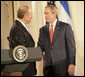 President George W. Bush and Prime Minister Ehud Olmert of Israel exchange handshakes Tuesday, May 23, 2006, at the end of a joint press availability in the East Room of the White House. White House photo by Eric Draper