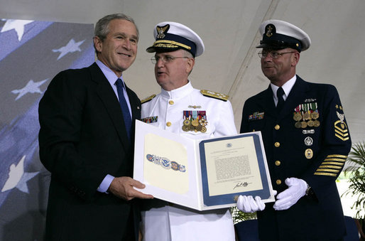 President George W. Bush presents Admiral Tom Collins, center, and Master Chief Petty Officer Frank Welch with the Presidential Unit Citation, Thursday, May 25, 2006 at Fort Lesley J. McNair in Washington, D.C., during the Change of Command Ceremony for the Commandant of the United States Coast Guard. White House photo by Eric Draper