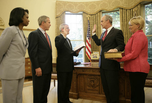 President George W. Bush is joined by Secretary of State Condoleezza Rice as Idaho Gov. Dirk Kempthorne is sworn into office as Secretary of the Interior by Chief of Staff Josh Bolten Friday, May 26, 2006. Mrs. Patricia Kempthorne holds the Kempthorne family Bible for the ceremony that was held in the Oval Office of the White House. White House photo by Eric Draper