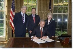 President George W. Bush is joined by Senator John Warner, R-Va, left, Senator Bill Frist, R-TN, center, and Congresswoman Virginia Foxx, R-NC, as he signs H.R. 1499, the Heroes Earned Retirement Opportunities Act, in the Oval Office Monday, May 29, 2006. White House photo by Paul Morse