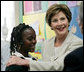 Mrs. Laura Bush congratulates Our Lady of Perpetual Help School student Rajanique White, 10, Monday, June 5, 2006, for the story Rajanique wrote and recited about a small accident that happened to her. Mrs. Bush visited the school to announce a Laura Bush Foundation for America's Libraries grant to Our Lady of Perpetual Help. White House photo by Shealah Craighead