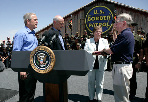 President George W. Bush stands with U.S.Homeland Security Secretary Michael Chertoff during the swearing-in ceremony of W. Ralph Basham, right, as the new Commissioner for U.S. Customs and Border Protection, Tuesday, June 6, 2006 at the Federal Law Enforcement Training Center Artesia Facility in Artesia, New Mexico. Commissioner Basham's wife, Judy Basham, holds the Bible during the ceremony. White House photo by Eric Draper