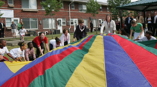 Mrs. Laura Bush joins the children and staff of the Meadowbrook Collaborative Community Center in playing with a colorful parachute during her visit to the facility Tuesday, June 6, 2006 in St. Louis Park, Minn. White House photo by Shealah Craighead