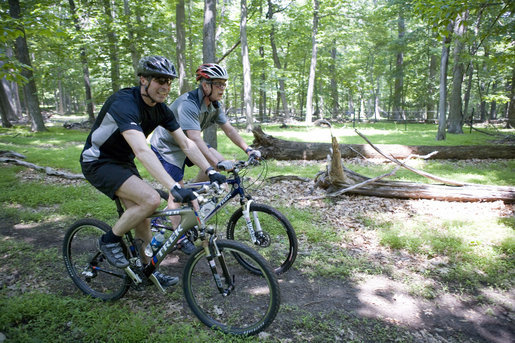 President George W. Bush and Prime Minister Anders Fogh Rasmussen of Denmark navigate a path at Camp David Friday, June 9, 2006. White House photo by Eric Draper