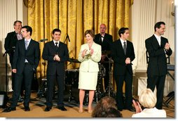 "Mrs. Laura Bush stands with members of the cast from the Tony award-winning musical ""Jersey Boys"" as they perform during a luncheon for Senate Spouses in the East Room, Monday, June 12, 2006. White House photo by Shealah Craighead"