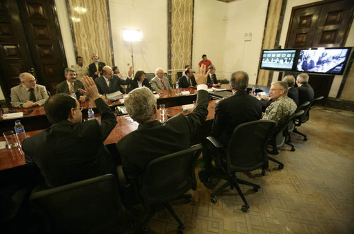 From Baghdad, President George W. Bush and Prime Minister Nouri al-Maliki of Iraq, wave to Vice President Dick Cheney, Secretary of State Condoleezza Rice and Secretary of Defense Donald Rumsfeld in Camp David, Md., during a teleconference Tuesday, June 13, 2006. White House photo by Eric Draper