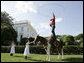 Children attending the annual Congressional Picnic on the South Lawn of the White House Wednesday evening, June 15, 2006, watch a rope trick cowboy entertainer. White House photo by Paul Morse