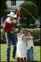 A rope trick cowboy lassos three children on the South Lawn of the White House as part of the entertainment at the annual Congressional Picnic Wednesday evening, June 15, 2006. White House photo by Kimberlee Hewitt