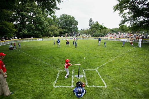 A member of the McGuire AFB Little League Yankees makes a hit on the South Lawn of the White House during action in the opening game of the 2006 Tee Ball season, Friday, June 23, 2006, between the McGuire AFB Yankees and the Dolcom Little League Indians of the Naval Submarine Base from Groton, Ct. White House photo by Paul Morse