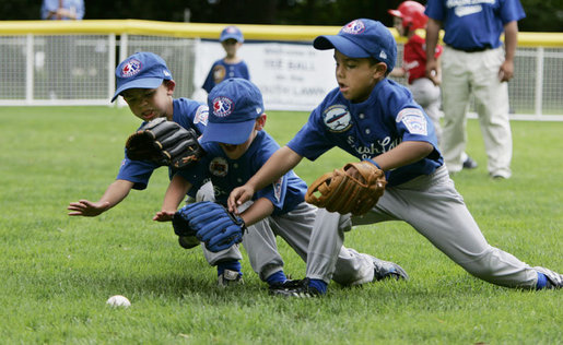 Three players for the Dolcom Little League Indians of the Naval Submarine Base in Groton, Ct., all dive for the ball on the South Lawn of the White House during action in the opening game of the 2006 Tee Ball season, Friday, June 23, 2006, between the McGuire Air Force Base Little League Yankees and the Dolcom Little League Indians. White House photo by Paul Morse