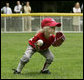 A member of the McGuire AFB Little League Yankees team fields the ball on the South Lawn of the White House during the opening game of the 2006 Tee Ball season, Friday, June 23, 2006, between the McGuire AFB Yankees and the Dolcom Little League Indians of the Naval Submarine Base from Groton, Ct. White House photo by Paul Morse