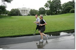 President George W. Bush runs with U.S. Army Staff Sergeant Christian Bagge, 23, of Eugene, Ore., on the South Lawn Tuesday, June 27, 2006. President Bush met Sgt. Bagge at Brooke Army Medical Center Jan. 1, 2006, where he promised to run with Sgt. Bagge. Since then, Sgt. Bagge has reenlisted to active duty. White House photo by Eric Draper