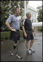 President George W. Bush and U.S. Army Staff Sergeant Christian Bagge, 23, of Eugene, Ore., talk with the media after their run on the South Lawn Tuesday, June 27, 2006. White House photo by Eric Draper
