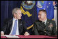 President George W. Bush talks with U.S. Army Sgt. First Class Kenneth Williams, as he meets with military personnel Wednesday, June 28, 2006, at the VFW Overland-St. Ann Memorial Post #3944 in St. Louis, Mo., who recently have returned from Iraq and Afghanistan. White House photo by Kimberlee Hewitt