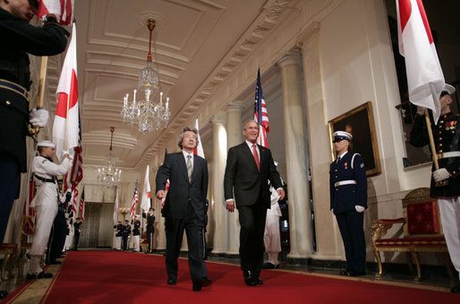 President George W. Bush and Japan's Prime Minister Junichiro Koizumi walk through Cross Hall on their way to a joint press availability Thursday, June 29, 2006, in the East Room of the White House. White House photo by Paul Morse