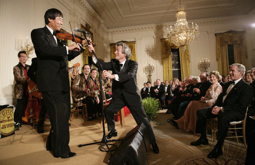 President George W. Bush watches as Japanese Prime Minister Junichiro Koizumi adjusts the microphone for country music entertainer Shoji Tabuchi Thursday evening, June 29, 2006 in the East Room of the White House, during the entertainment following the official dinner in honor of Koizumi's visit to the United States. White House photo by Eric Draper