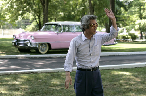 Japan's Prime Minister Junichiro Koizumi stands before a classic pink Cadillac and waves to reporters as he wears a pair of Elvis Presley style sunglasses during his tour Friday, June 30, 2006 of Presley's mansion, Graceland, with President George W. Bush and Mrs. Laura Bush in Memphis. White House photo by Eric Draper
