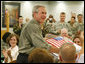 President George W. Bush is presented with a birthday cake in honor of his upcoming 60th birthday, at a luncheon with troops Tuesday, July 4, 2006, at Fort Bragg in North Carolina. President Bush earlier addressed the troops at an Independence Day celebration thanking them for their service to the nation. White House photo by Paul Morse