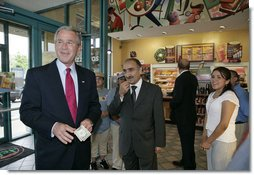"President George W. Bush offers to buy a cup of coffee for a member of the media during a stop at Dunkin' Donuts in Alexandria, Va., July 5, 2006. ""We need to make sure we help people assimilate. I met four people here who assimilated into our country. They speak English; they understand the history of our country; they love the American flag as much as I love the American flag,"" said the President. ""That's one of the great things about America, we help newcomers assimilate. Here's four folks that are living the American Dream, and I think it helps renew our soul and our spirit to help people assimilate."" White House photo by Kimberlee Hewitt"