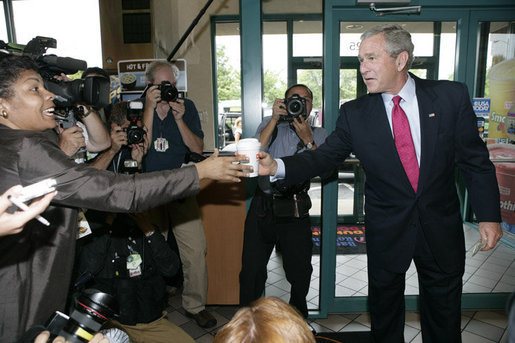 President George W. Bush offers to buy a cup of coffee for a member of the media during a stop at Dunkin' Donuts in Alexandria, Va., July 5, 2006, where President Bush spoke in support of the Basic Pilot Program to verify employment eligibility. White House photo by Kimberlee Hewitt