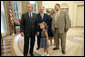 President George W. Bush and 5-year-old Alexa Ostolaza, the 2006 March of Dimes National Ambassador, peek out an Oval Office window for the President's dogs Thursday, July 6, 2006. With them, from left, are Jim Sproull Jr., Chairman of the Board of the March of the Dimes, and Alexa's parents Jessica and Josue Ostolaza. White House photo by Kimberlee Hewitt