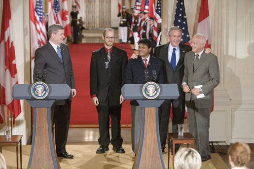 After holding a press conference with Canadian Prime Minister Stephen Harper, President George W. Bush poses with fellow birthday celebrants in the East Room Thursday, July 6, 2006. The President celebrates his 60th birthday today. Pictured with him are, from left. Todd Mizis of the U.S. State Department; Raghubir Goyal of the India Globe and Asia Today; and Richard Benedetto of USA Today. White House photo by Kimberlee Hewitt