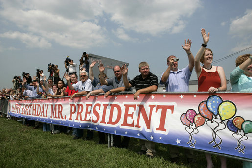 Standing behind a banner wishing President George W. Bush a happy birthday a crowd waves to President Bush, who celebrated his 60th birthday Thursday, as he departs from Chicago, Friday, July 7, 2006. White House photo by Eric Draper