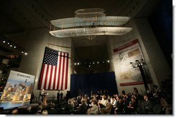 President George W. Bush speaks beneath a replica of the Wright Brother's plane as he addresses a news conference at the Museum of Science and Industry in Chicago, Friday, July 7, 2006, speaking on the economy, immigration reform and security issues. White House photo by Eric Draper