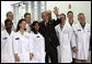 President George W. Bush stands with a group of employees as he waves to others during a tour of the Cabot Microelectronics Corporation facility in Aurora, Ill., Friday, July 7, 2006. White House photo by Eric Draper